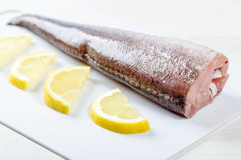 Nahaufnahme zeigt ein Stück Hechtfisch, roh, neben halbierten Zitronenscheiben