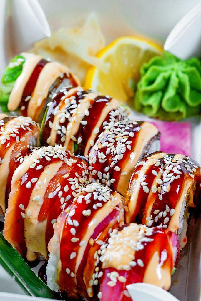 Nahaufnahme zeigt eingelegte Sushi-Rollen mit Ingwer, dem japanischen Meerrettich Wasabi und Zitronenscheibe in einer Lebensmittelbox