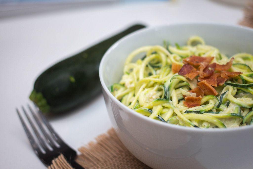 Nahaufnahme - Zucchini Nudeln - Zoodles - mit knusprigem Speck
