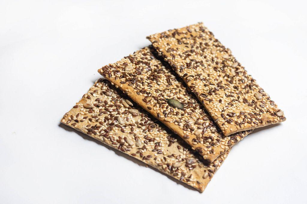 Nahrhafte Kräcker als Snack mit Sesam, Leinsamen und Sonnenblumenkernen vor weißem Hintergrund