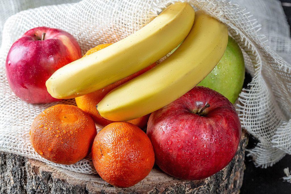Nasse Äpfel, Bananen, Mandarinen und Orangen auf einem Leinentuch auf einem Baumstamm