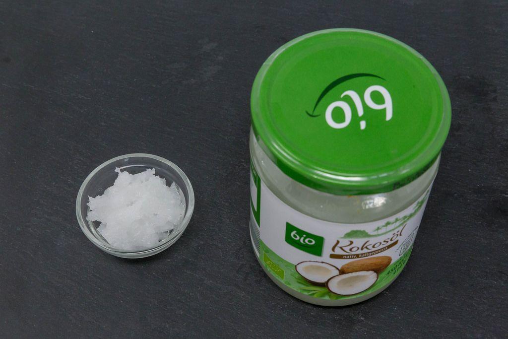 Natives Kaltgepresstes Bio-Kokosöl im Glas mit Muster in Schale daneben auf schwarzer Schieferplatte
