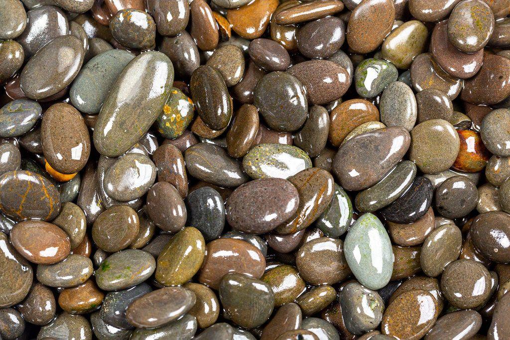 Naturally polished dark rock pebbles background