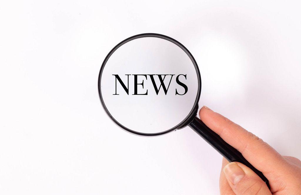News  unter der Lupe auf weißem Hintergrund