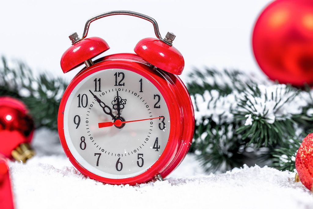 Nice New year background with red alarm clock, toys and gifts in the snow