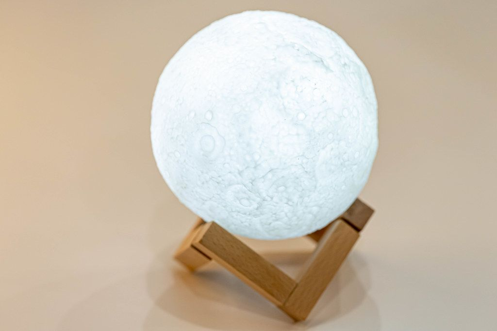 Night light in the form of a shining moon on a wooden stand (Flip 2019)