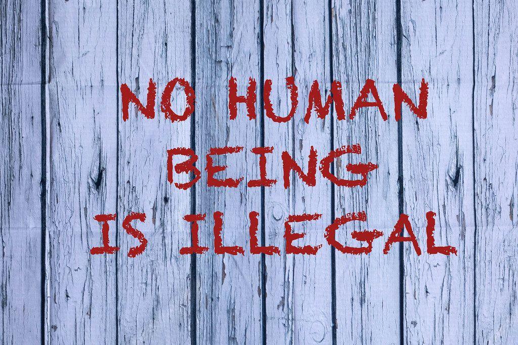 No human is illegal geschrieben auf einer weißen Holzfassade