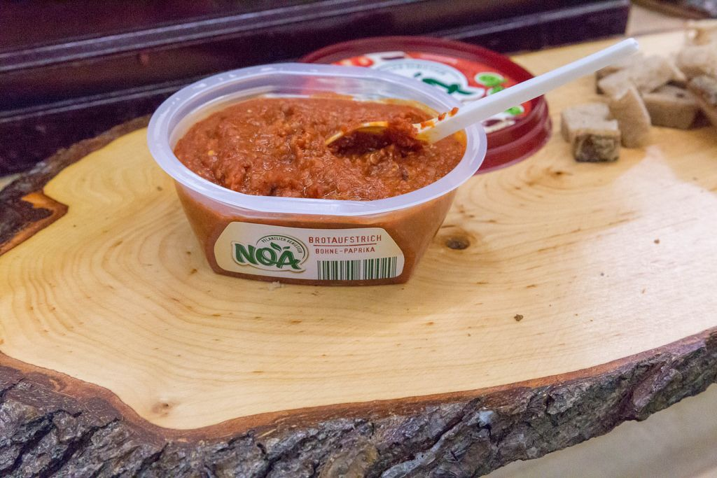 Noa - Bohnen-Paprika Brotaufstrich mit Brot auf einer Holzplatte