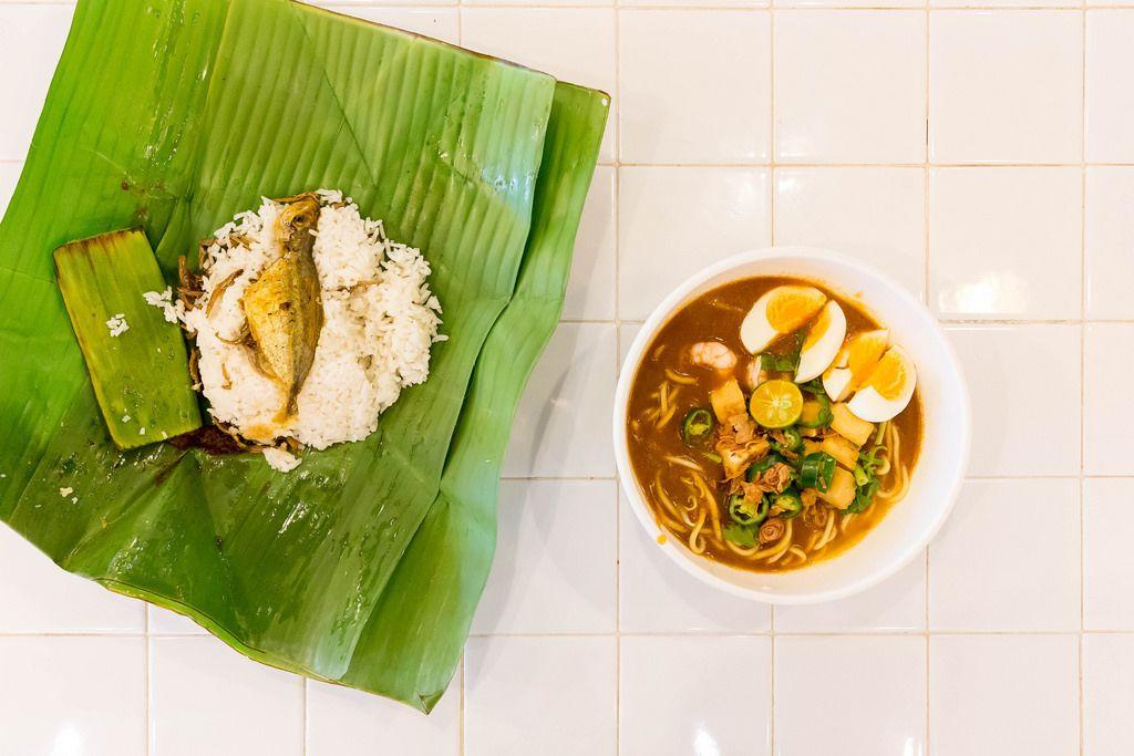 Nudeln mit Garnelen, Eiern und Paprika mit Fisch und Reiß im Palmenblatt