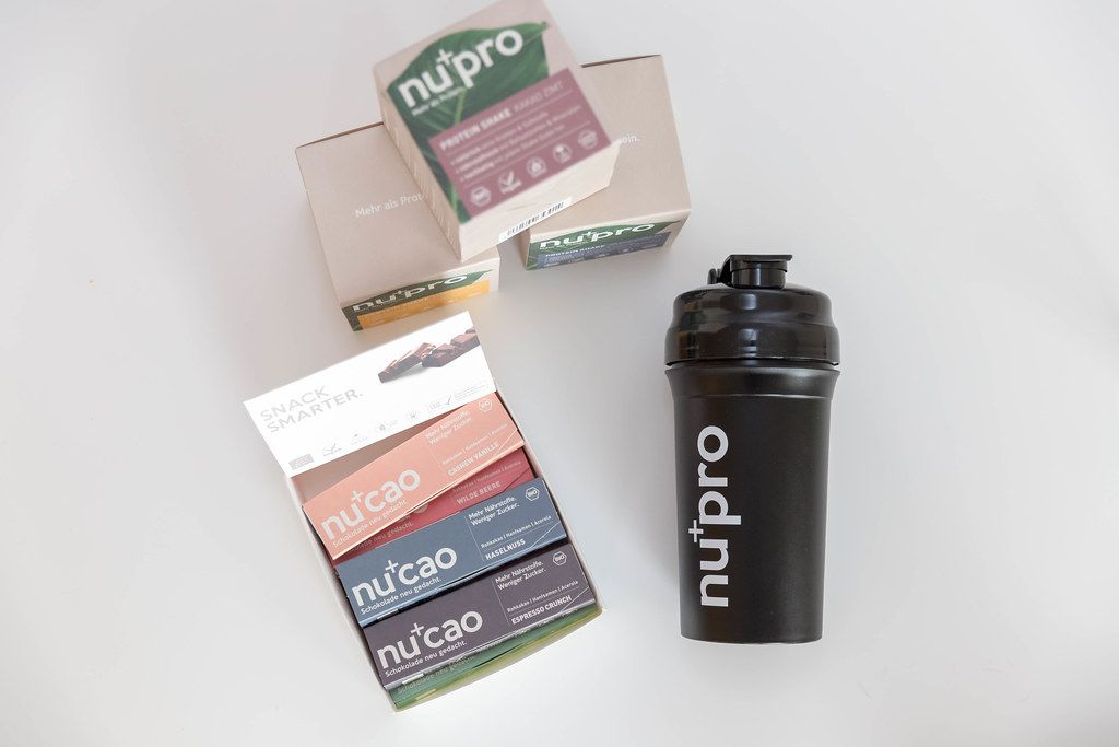 NuPro protein shakes for muscle building and raw cocoa NuCao, in various flavours, stacked on a white surface next to a drinking bottle