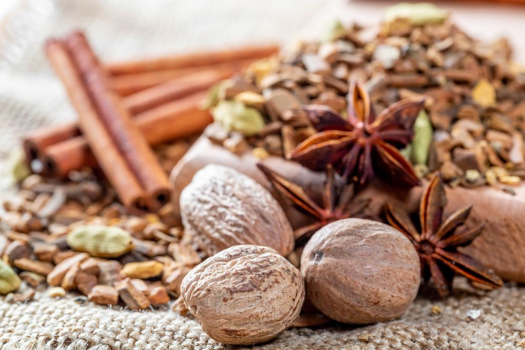 Nutmeg, cloves, cinnamon sticks, star anise and other spices, roots and bark in dried tea on burlap background