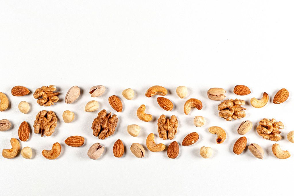 Nuts of different types on a white background with free space, top view