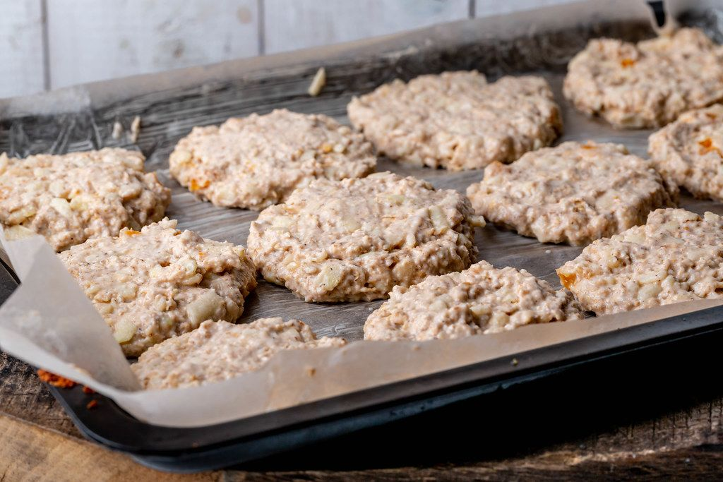 Oatmeal cookies dough with apples and dried apricots on a baking sheet before baking