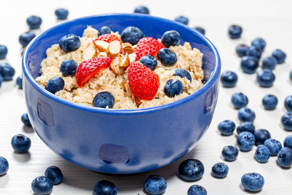Oatmeal with fresh blueberries, almonds and strawberries in a blue bowl