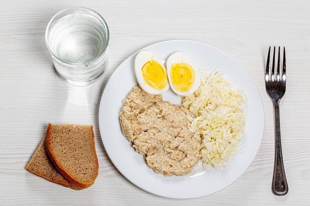 Oatmeal with fresh cabbage salad and boiled eggs on a white table with black bread and a glass of water