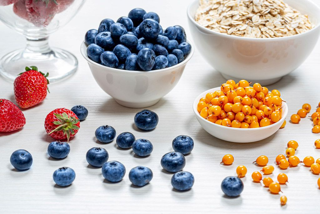 Oatmeal with fresh strawberries, sea buckthorn and blueberries in white bowls