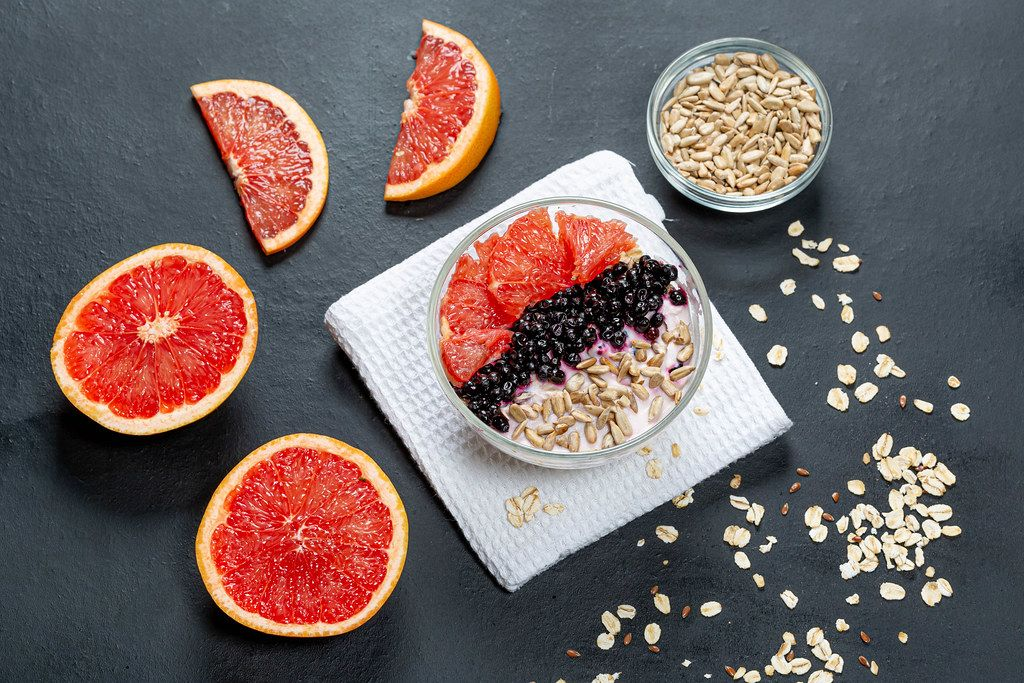 Oatmeal with grapefruit, black elderberry and sunflower seeds on a black background. Top view