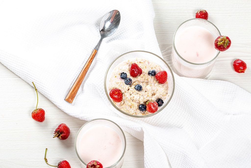 Oatmeal with strawberries and blueberries and yogurt on the white table. Top view