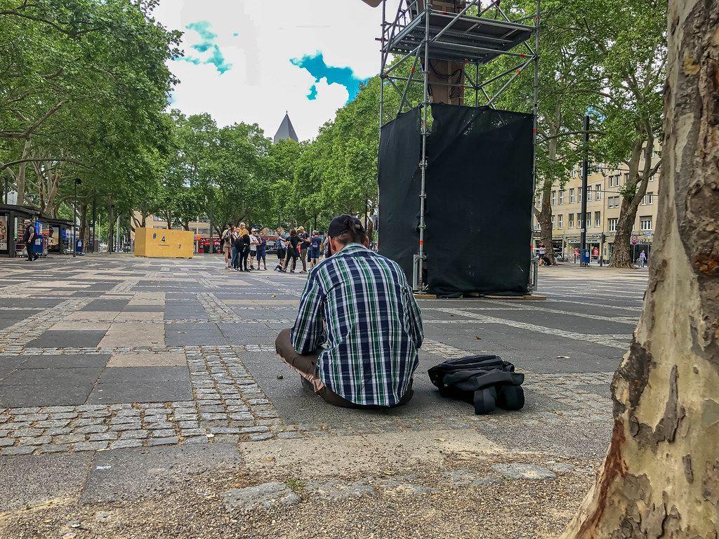 Obdachloser Mann sitzt auf dem Neumarkt, vor Besucher des Kölner Kunstfestivals