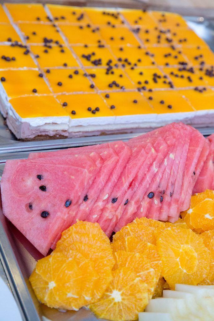 Obstplatte mit Wassermelone und Orange und eine Orangentorte im Hintergrund