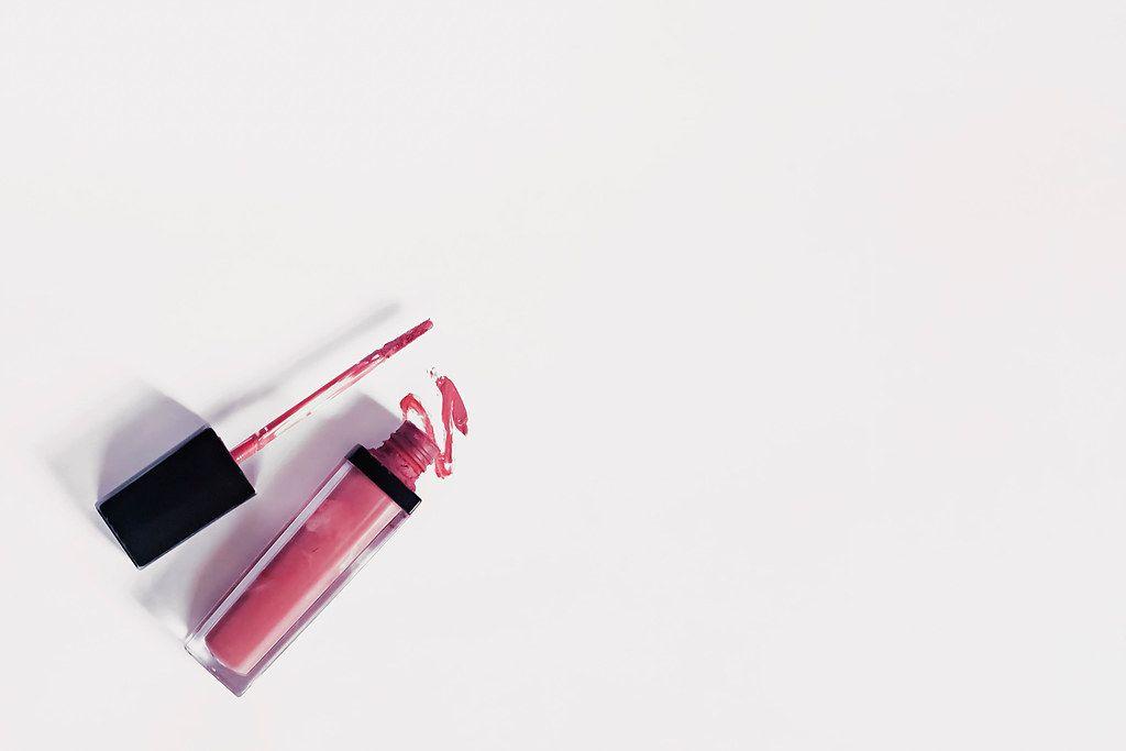Offene Nagellackflasche und Farbstrich auf weißem Papierhintergrund