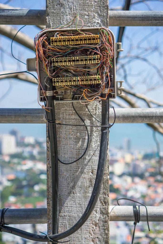 Offener Sicherungskasten mit diversen Elektrokabeln vor der Stadt Vung Tau im Hintergrund