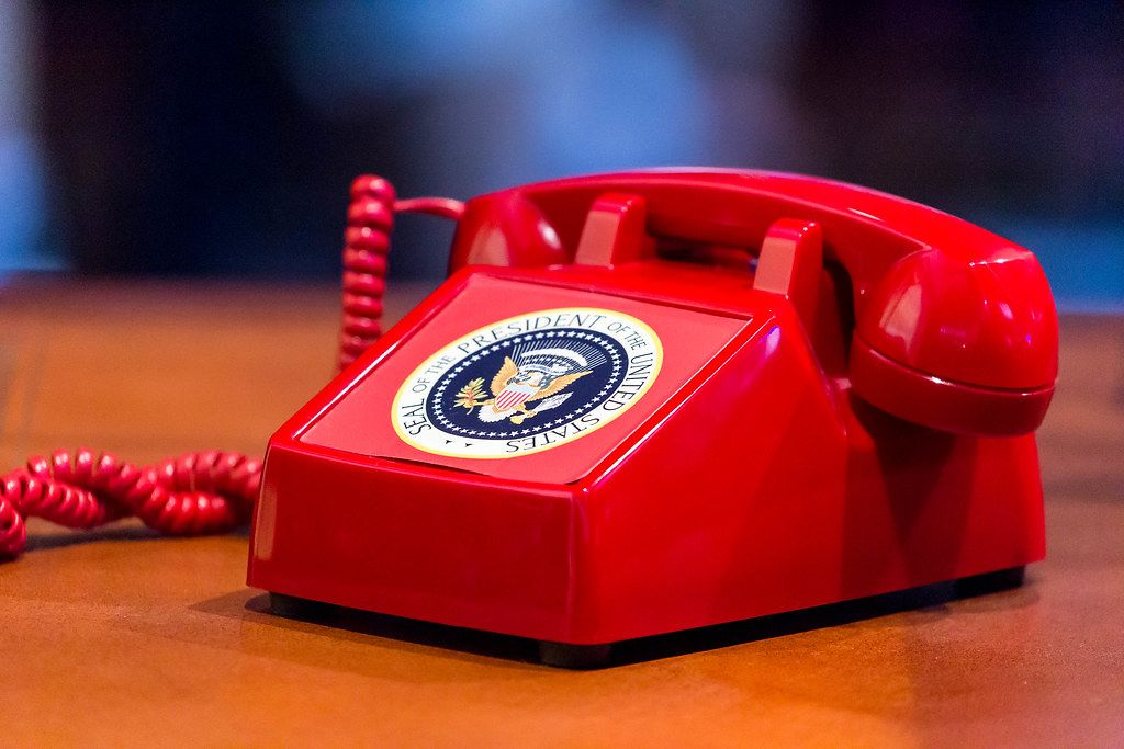 Old red vintage phone with Seal of the president of the united states as a sticker on it