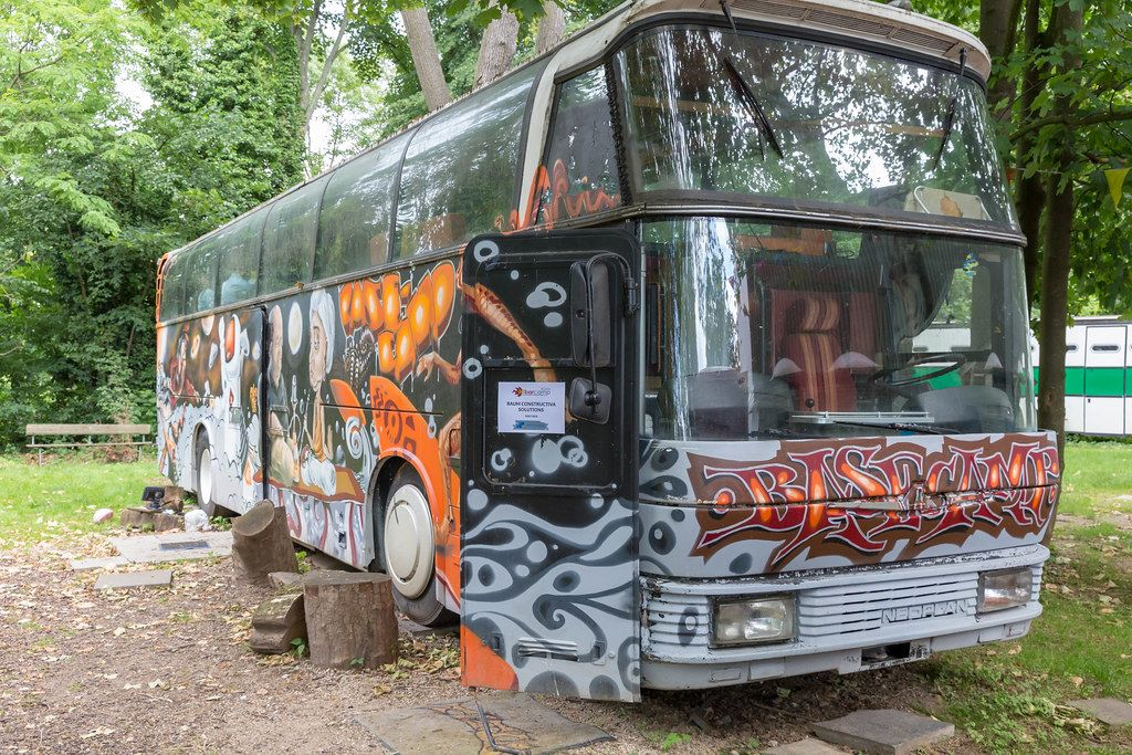 Old retro bus full of graffities with BaseCamp sign in the front at the BaseCamp youth hostel in Bonn