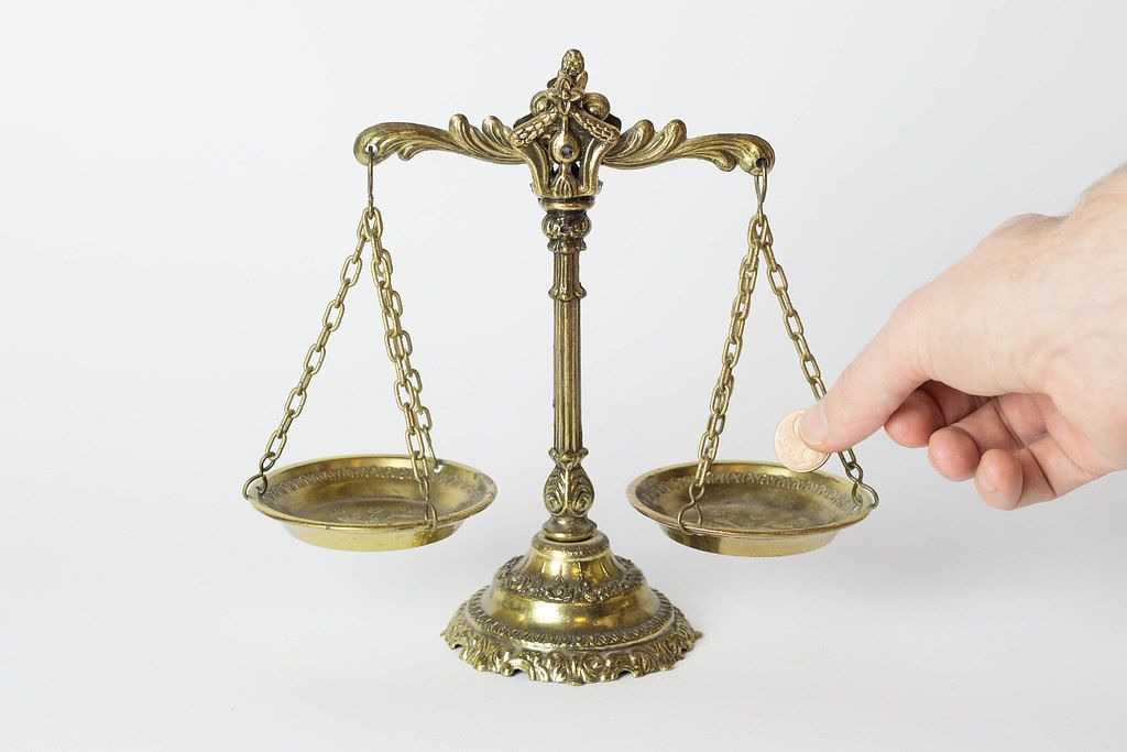 Old-School Golden scale in balance with a hand putting a coin on it