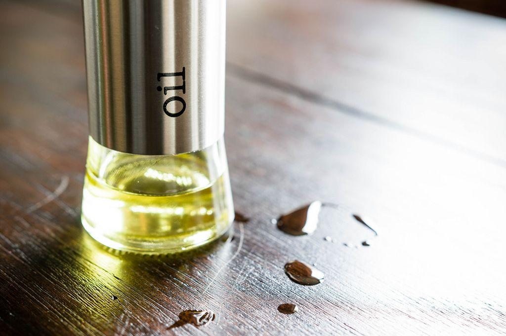 Ölflasche auf einem dunklen Holztisch