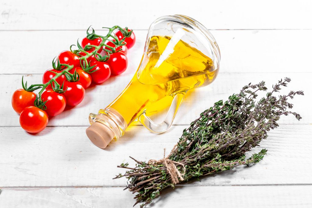 Olivenöl in einer Karaffe, Tomatenstaude und gebundene Thymian-Kräuter, liegend auf einem weißen Holztisch