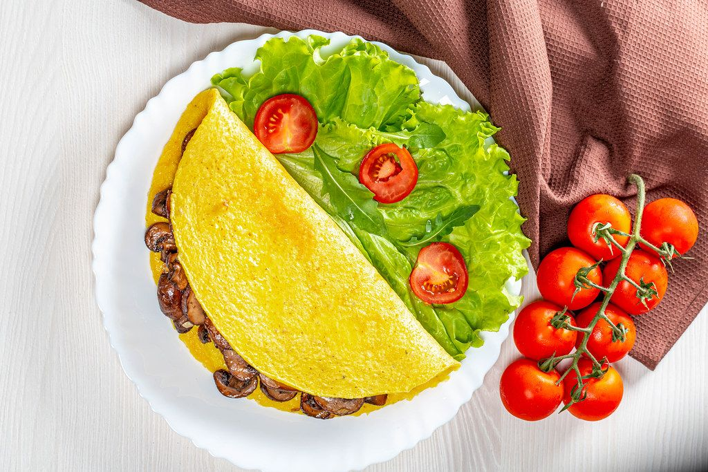Omelet stuffed with fried mushrooms with fresh lettuce and tomatoes