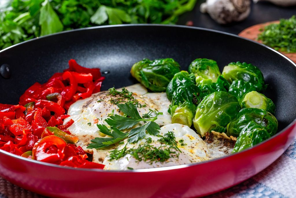 Omelet with Brussels sprouts and bell pepper in a frying pan