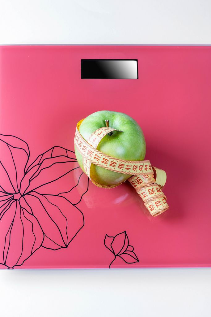 On the scales is a measuring tape and a green Apple-the concept of weight loss