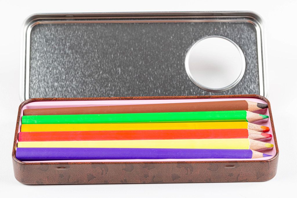 Open iron box with colored pencils