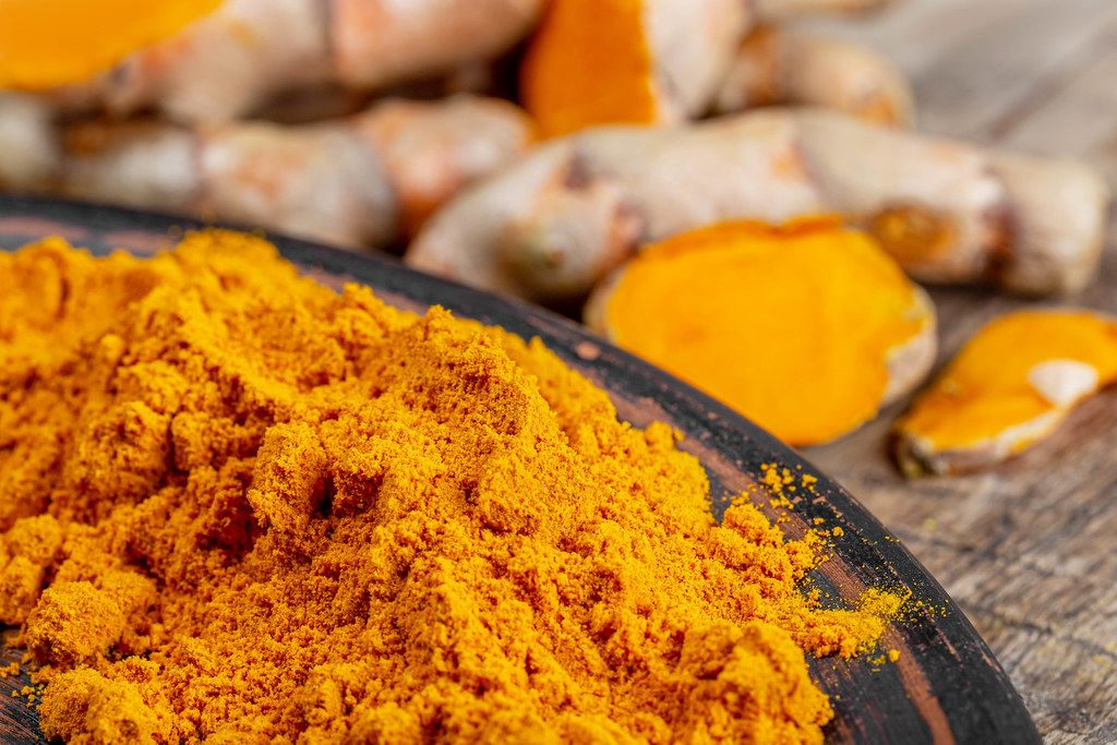 Orange turmeric powder with fresh turmeric