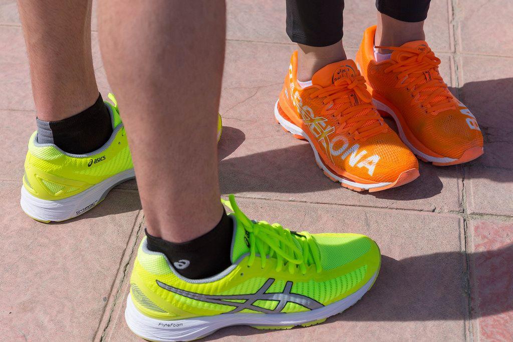 Orangefarbene und hellgrüne ASICS Laufschuhe
