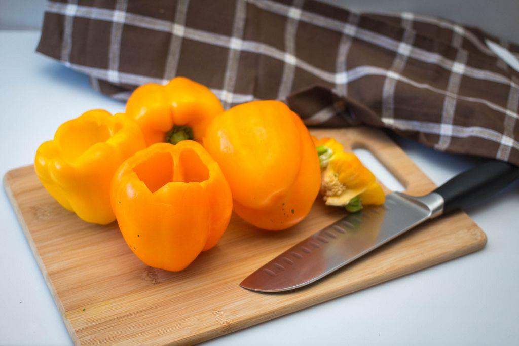Orangenfarbige Parpika auf einem Schneidebrett mit Santoku-Küchenmesser und einem Tuch im Hintergrund