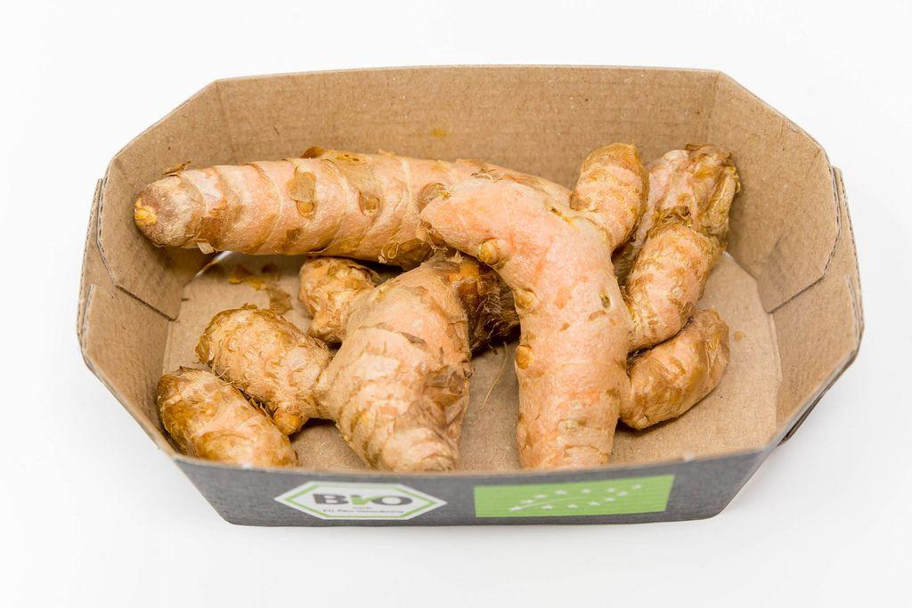 Organic turmeric rhizomes in a cardboard box