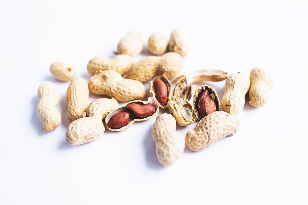 Organic whole in-shell peanuts on white background