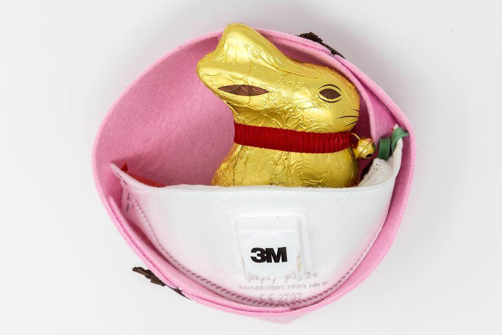 Ostern feiern in Corona-Zeiten: Lindt Goldhase und FFP3 Atemschutzmaske von 3M in Ostern-Deko vor weißem Hintergrund