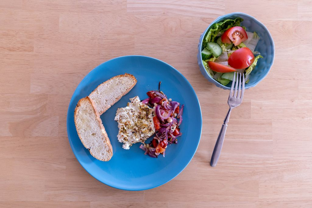 Oven-baked shepherd feta cheese with tomatoes, red onions and garlic bread on a blue plate with a fresh mixed salad in a bowl