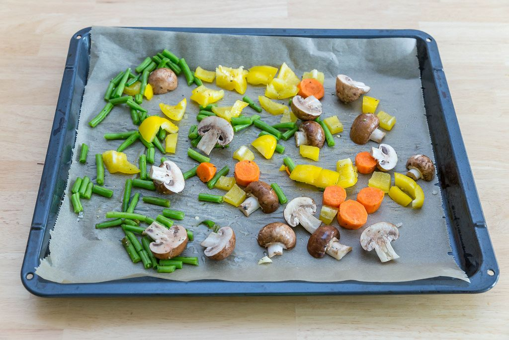 Oven-roasted vegetables on baking paper prior to roasting