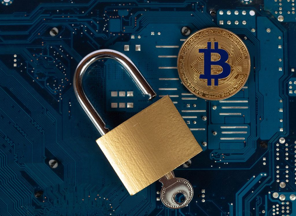 Padlock with golden Bitcoin on computer parts