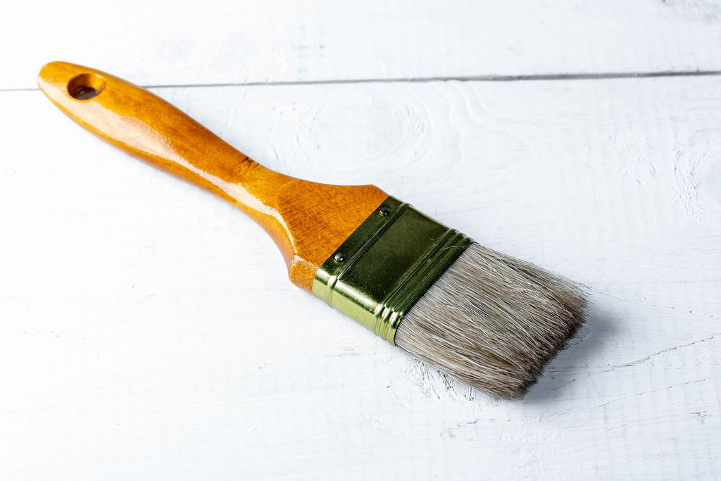 Paint brush on white wooden background