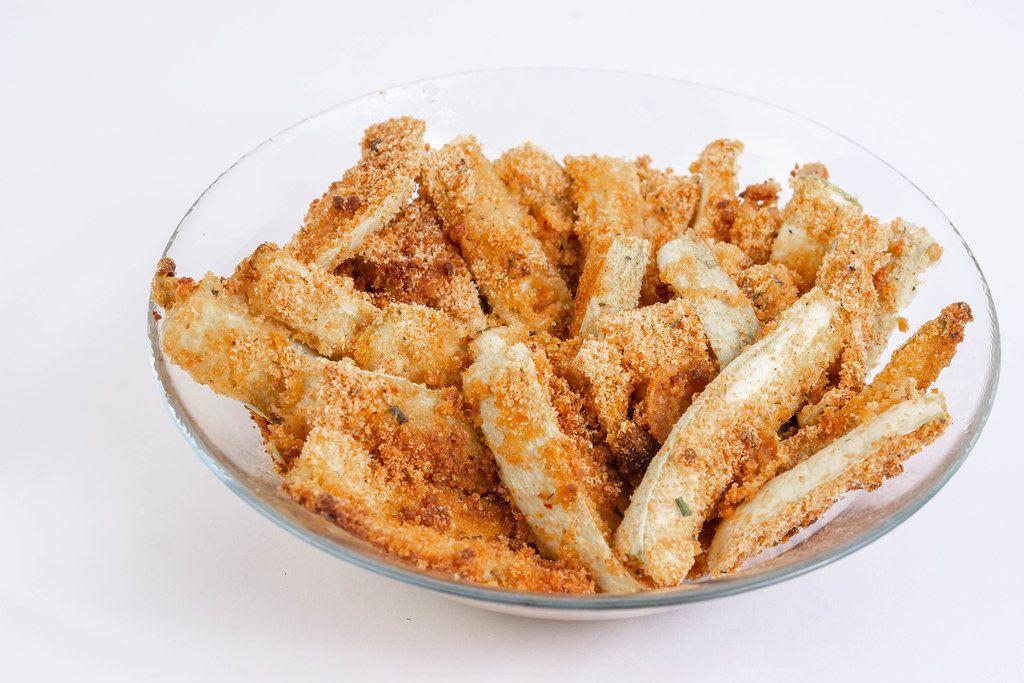 Panierte, gebackene Zucchini mit Brotkrümmel, isoliert vor weißem Hintergrund