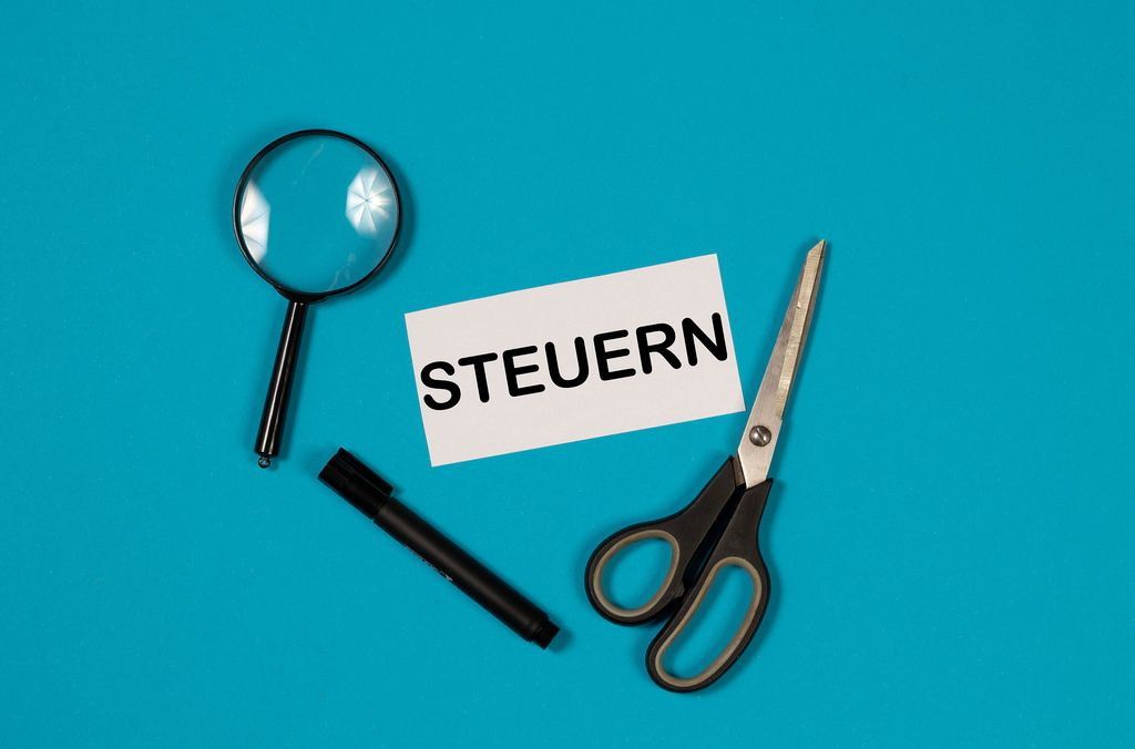 Paper with word Steuern and scissors on blue background