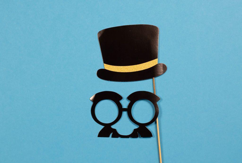 Papierhut und Brille mir Schnurrbart an Holzstab auf blauem Hintergrund