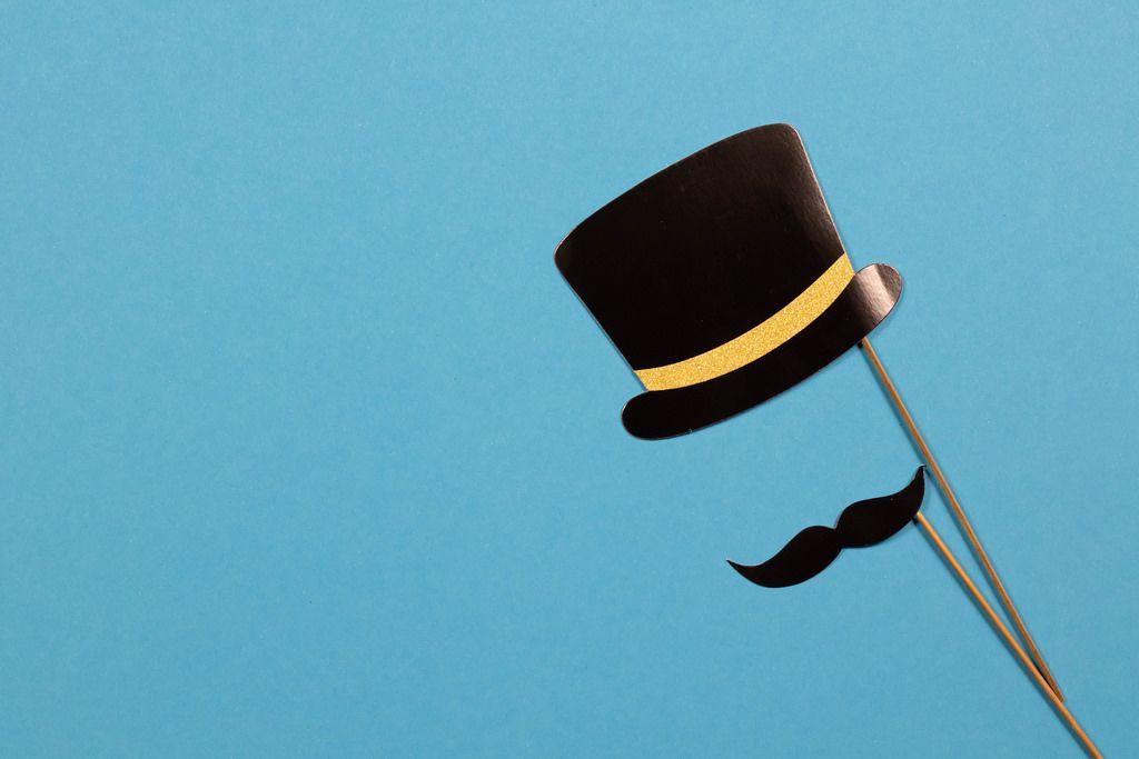 Papierhut und Schnurrbart an Stielen auf blauem Hintergrund