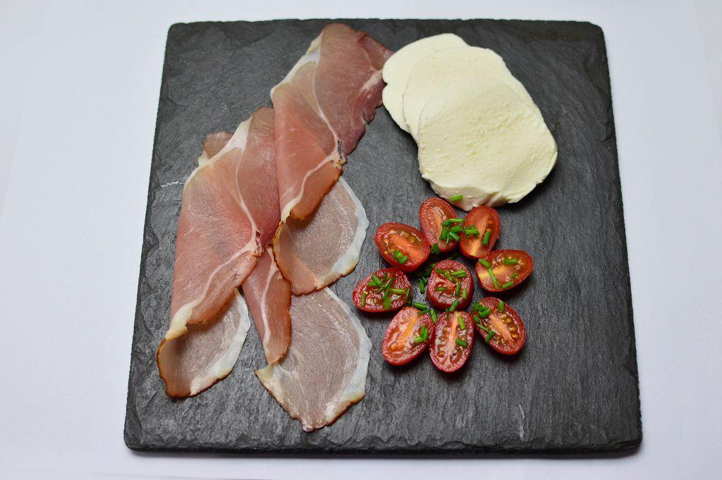 Parmaschinken mit Mozzarella und Kirschtomaten auf einer Schieferplatte